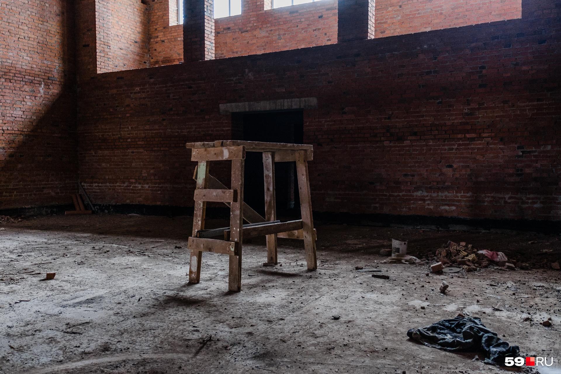 Внутри здания рабочие оставили козлы, тряпки, пустые пластиковые бутылки