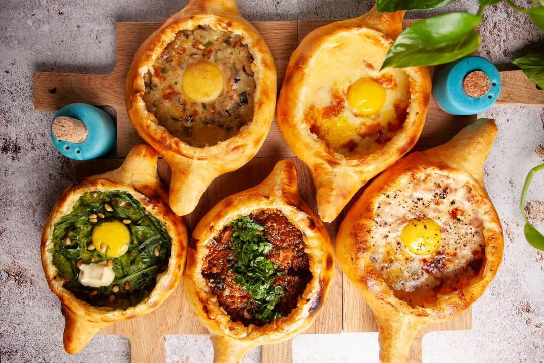 Хачапури по-аджарски с начинками: шпинат и кедровые орешки, грибы и домашний сыр, аджапсандали и домашний сыр; традиционное аджарское хачапури и хачапури с домашним сыром, ветчиной и жареным луком
