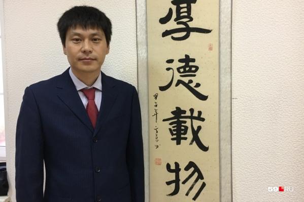 Лю Янькунь стоит у надписи на его родном языке, каждый иероглиф обозначает качество настоящего учителя