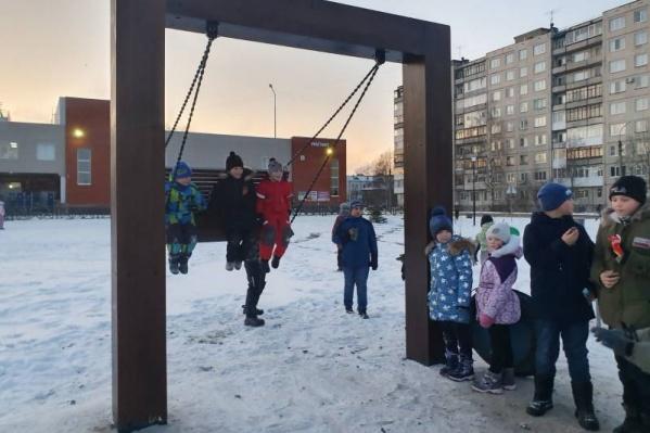 Дети, гуляющие в парке, ждут своей очереди, чтобы прокатиться на качелях