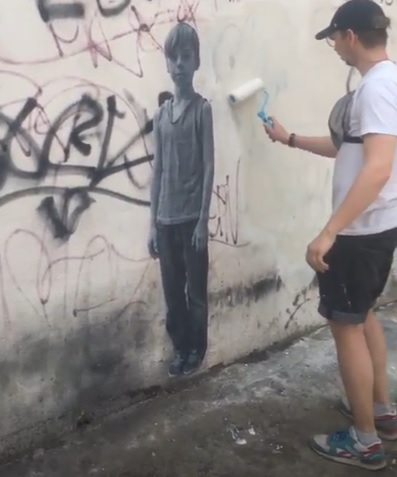 Иван закрашивает стену под надпись «Привет Максиму от москвичей»