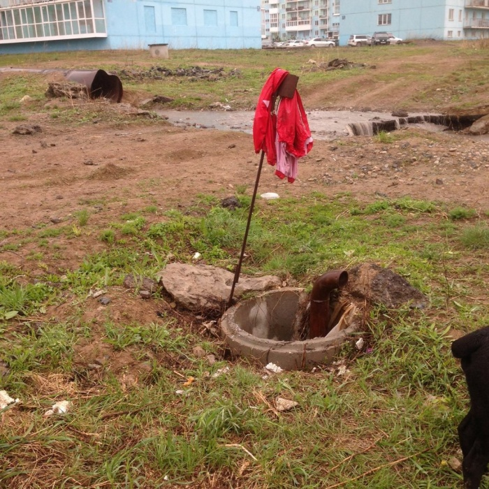 Люк, в который провалился кане-корсо. Хозяева обозначили опасное место порванным красным комбинезоном собаки