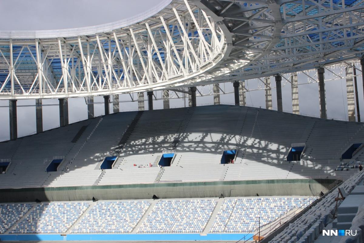 Солнце через открытую крышу (это требование ФИФА) проникает на трибуну.