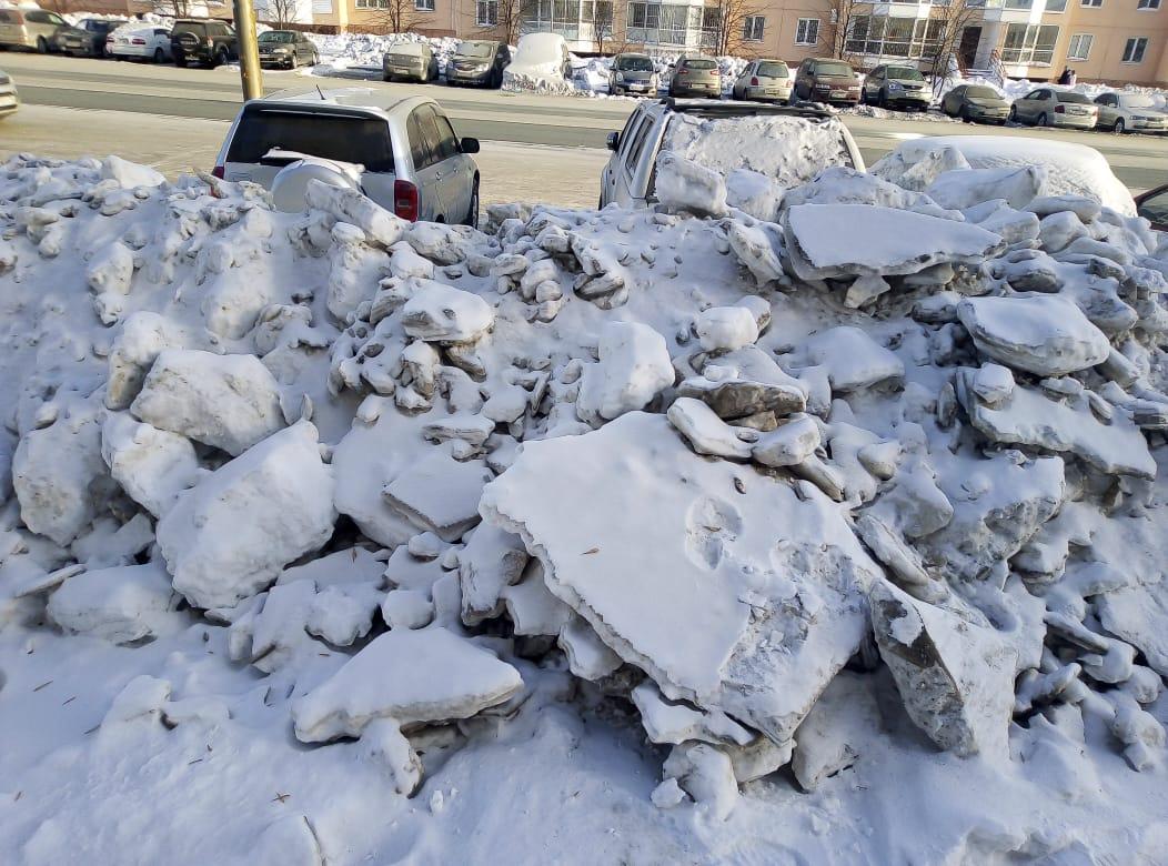 На пути от парковки к тротуарам возле Гребенщикова,13 лежат замёрзшие глыбы снега