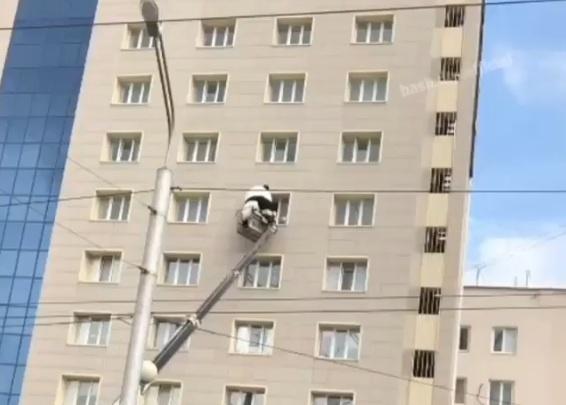 В Уфе гигантская панда поднимается на кране в окно высотки