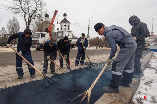 На морозе рабочие заливают дорожки, которые должны были сдать ещё 25 октября