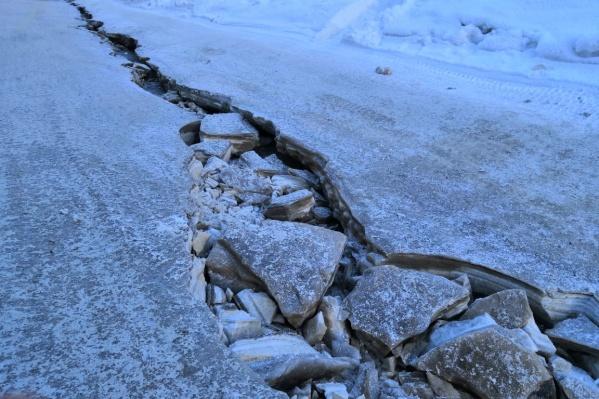 На улице Федосеева люди вынуждены пробираться к жилмассиву через трещину на дороге, покрытой льдом