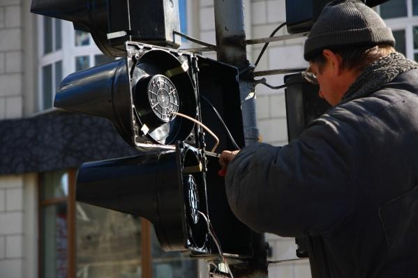 Бригада ремонтников уже приехала на место и пытается включить погасшие светофоры