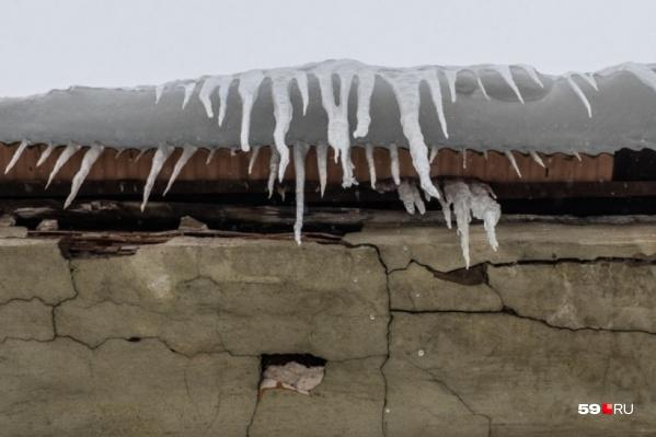 На некоторых крышах лед и снег до сих пор убрали не полностью