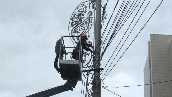 По городу рабочие снимают праздничную иллюминацию