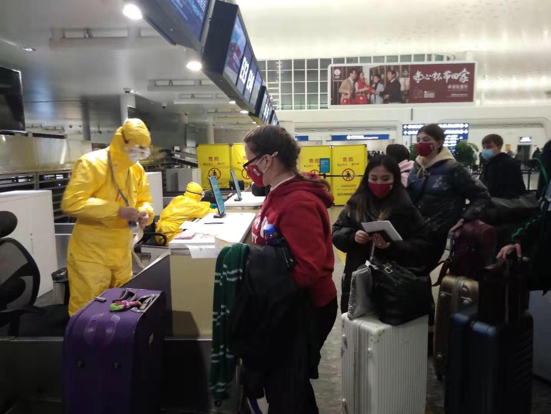На стойках регистрации работают люди в защитных костюмах