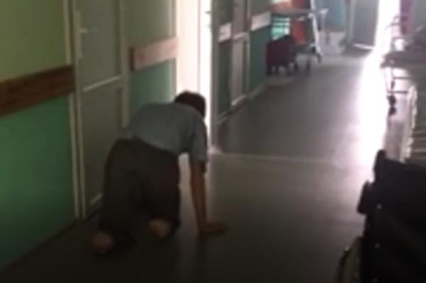 На видео мы видим мужчину без ног, который ползает по полу. Рядом — ни одного медработника