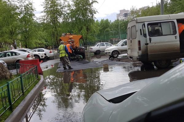 Мужчины укладывают асфальт около огромной лужи на улице Садовой