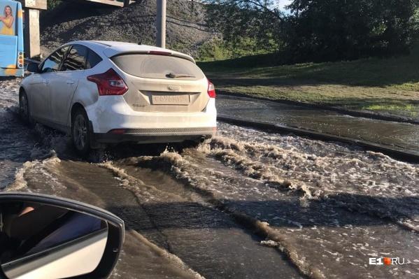 Из-за потопа машины с трудом преодолевают участок под мостом