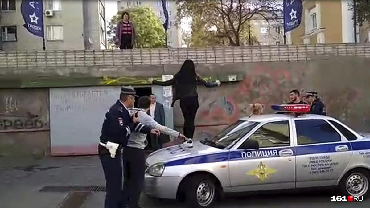 Одна из девушек забралась на патрульный автомобиль и прыгала на нем
