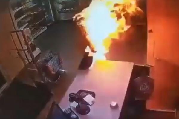 Скриншот видео: женщина, объятая огнем, выбегает из подсобки