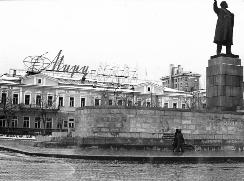 На здании за памятником Ленину раньше была фраза «Миру — мир», а сейчас — реклама одного из банков