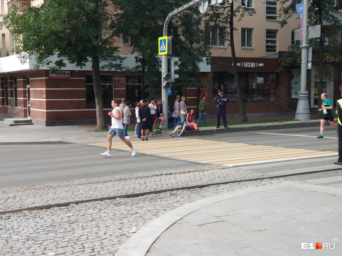 Молодой парень лежит на тротуаре на перекрёстке Сакко и Ванцетти — Ленина. До финиша он не добежал