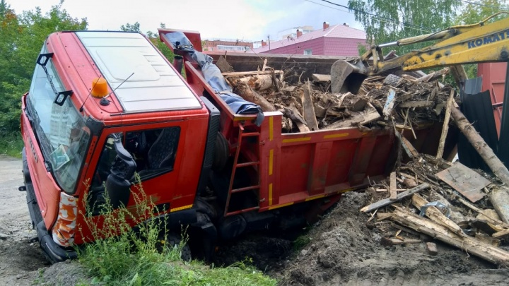 На Уралмаше грузовик, вывозя снесенный дом, провалился в ливневку и опрокинул забор