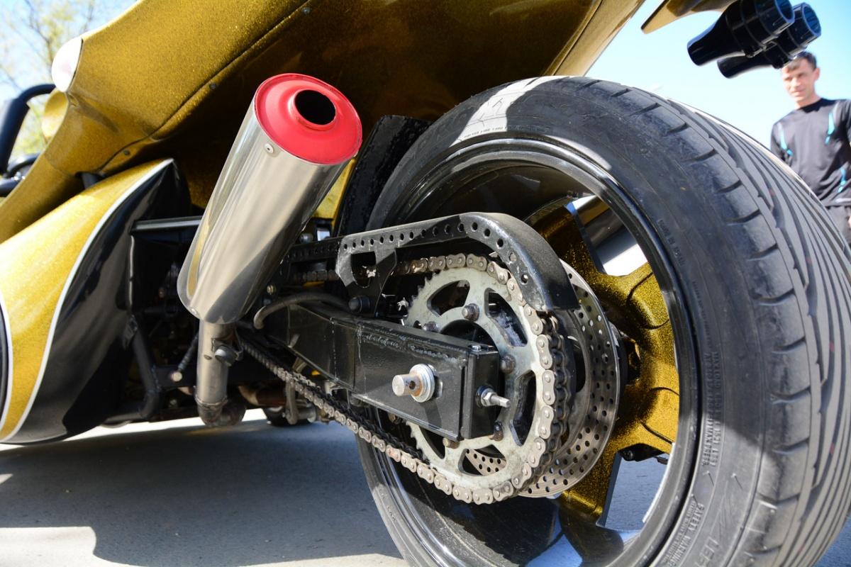Маятник подвески, звездочка привода и дисковые перфорированные тормоза. То, что это трайк, видно по плоскому в поперечнике профилю шины — она здесь автомобильная