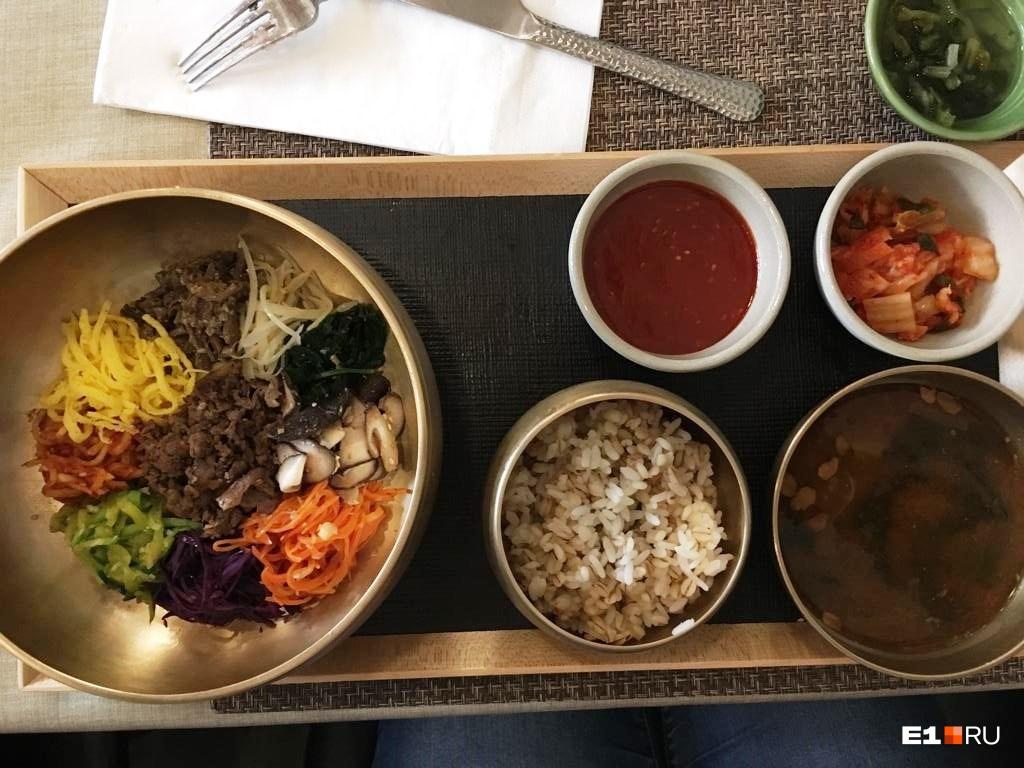 Рис из чашки добавляют в миску с овощами и мясом, заправляют соусом и перемешивают