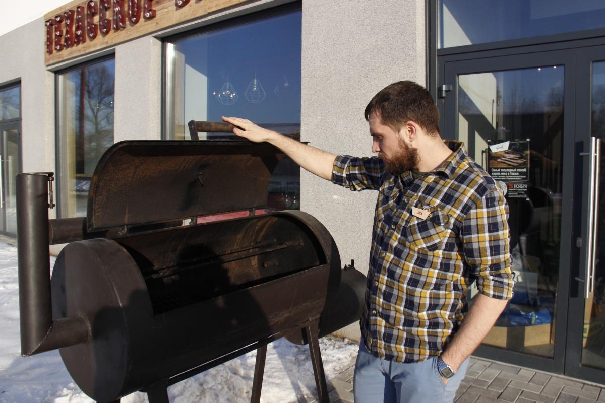 Евгений Кулышев показывает передвижную коптильню, которую заведение использует для выездных мероприятий.