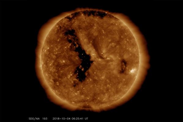 Заряженные частицы, которые направляются к Земле, испустила «корональная дыра» на Солнце — на фото это чёрная область