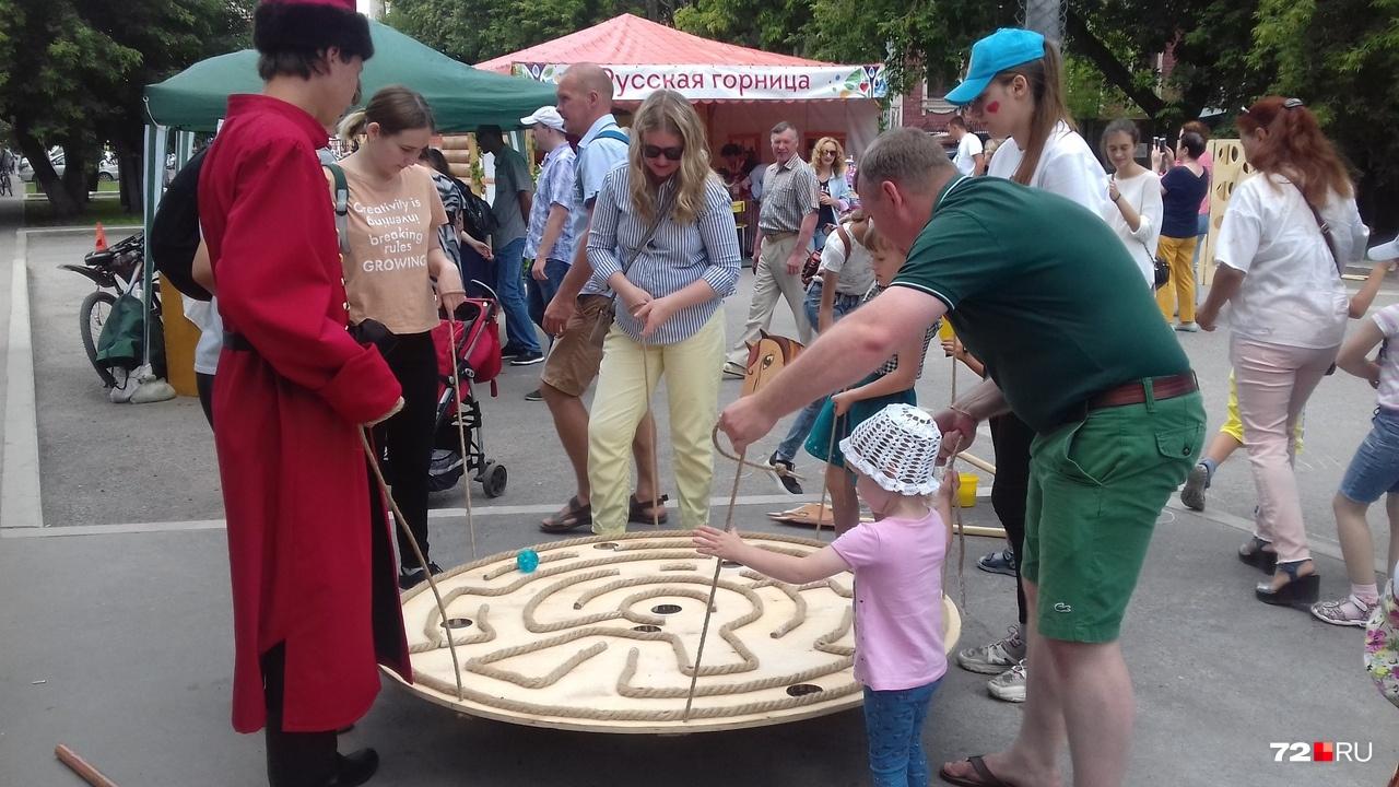 На перекрестке Дзержинского — Володарского — русские забавы: нужно забросить кольцо на деревянного гуся, пройти на ходулях, всей семьей забросить шар в лунку. А у вас бы получилось?