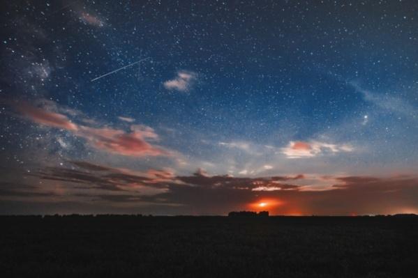 На фото — метеоры потока Персеиды, снятые в 2018 году, сейчас этот поток также можно видеть в небе