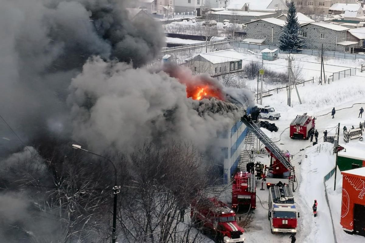 Пожарные тушат огонь с автолестницы