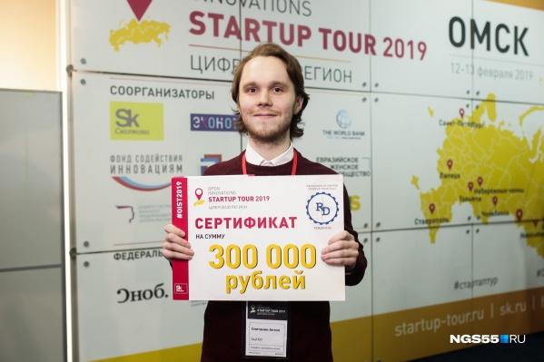Антон Сметанин показывает свой сертификат на 300 тысяч