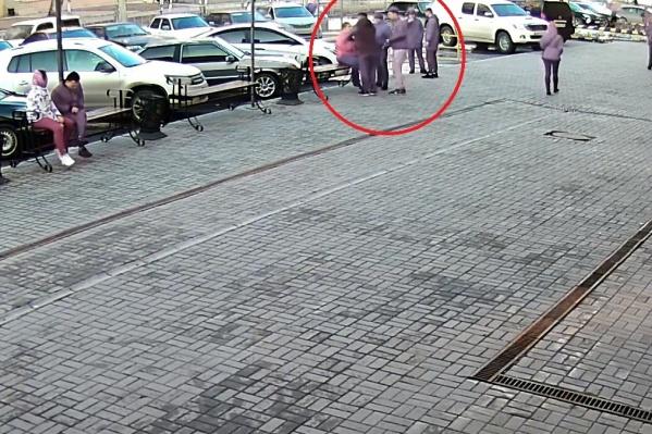 Люди сидели на скамейке и смотрели, как в машину заталкивают человека