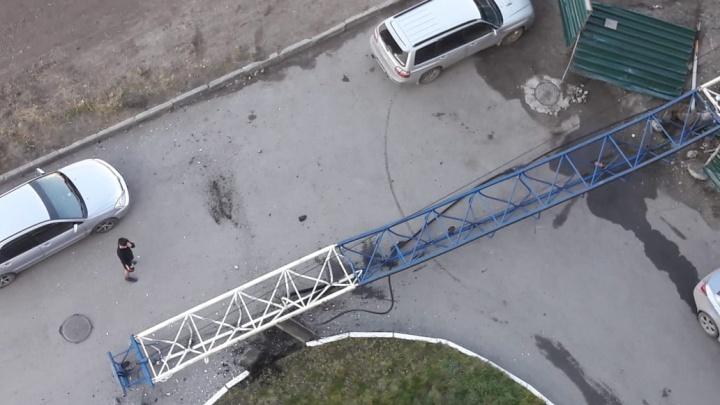 Строительный кран упал во двор с машинами