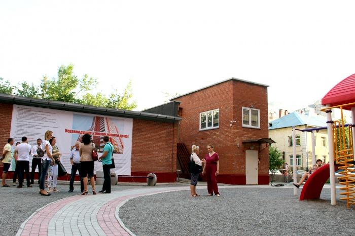 Жители дома по улице Орджоникидзе собрались у баннера с рекламой кандидатов, которую правление ТСЖ снять не может — баннер висит на стене чужого здания