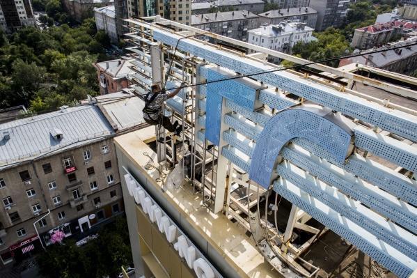 Сейчас на крыше здания можно увидеть рабочих, которые разбирают логотип НГС