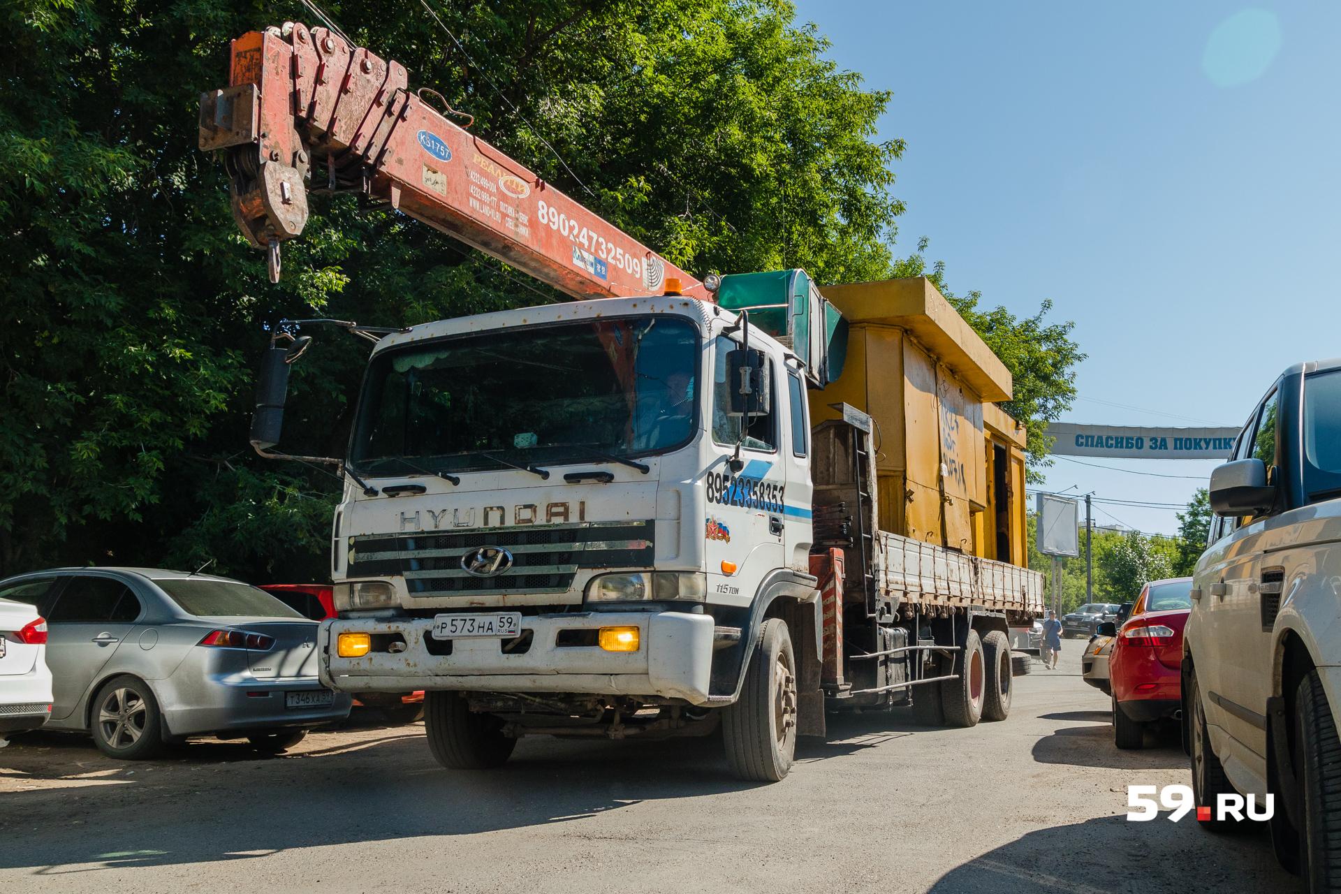 Автокран увозит демонтированные киоски