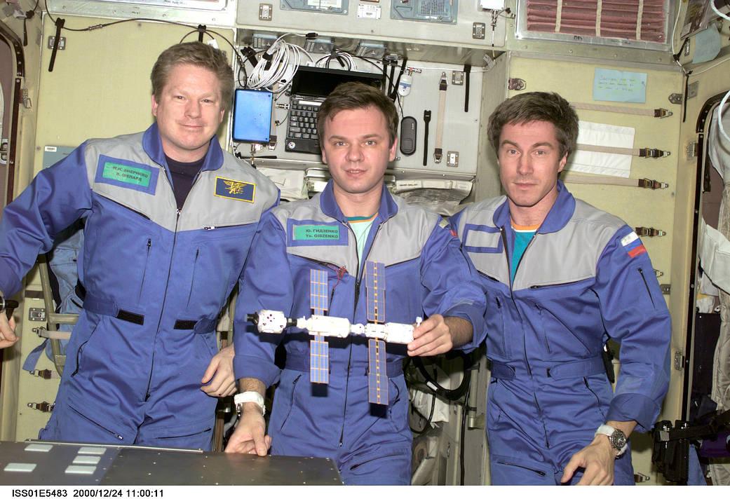 Экипаж первой миссии МКС-1 в составе (слева направо) Билла Шеппарда, Юрия Гидзенко и Сергея Крикалева. В руках у Гидзенко модель станции на тот момент — из двух российских блоков и одного американского