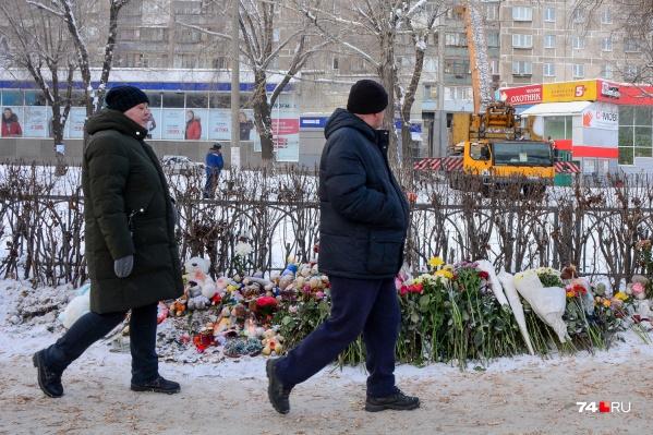 С внешней стороны дома на Карла Маркса, 164 люди кладут цветы