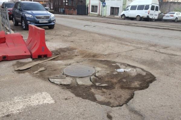 Автомобили царапают колодец дном, пытаясь проехать злополучное место и выехать на Ленина
