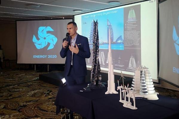 Денис Тяглин показал, как должен выглядеть его ветроэлектрогенератор (на фото — чёрного цвета справа от изобретателя) в сравнении с 828-метровым небоскрёбом «Бурдж-Халифа» в Дубае