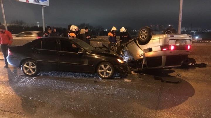 На Октябрьском мосту перевернулся ВАЗ: людей зажало в машине