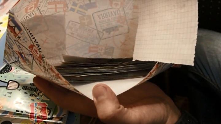 Конверты с пачками наличных и непонятные журналы: полицейские показали видео обысков у ритуальщиков