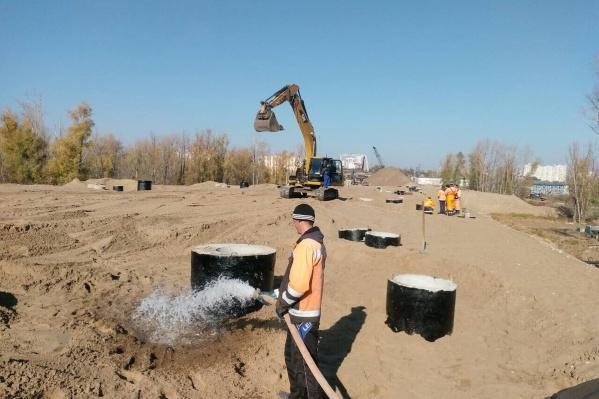 Рабочие проливают песок для утрамбовки