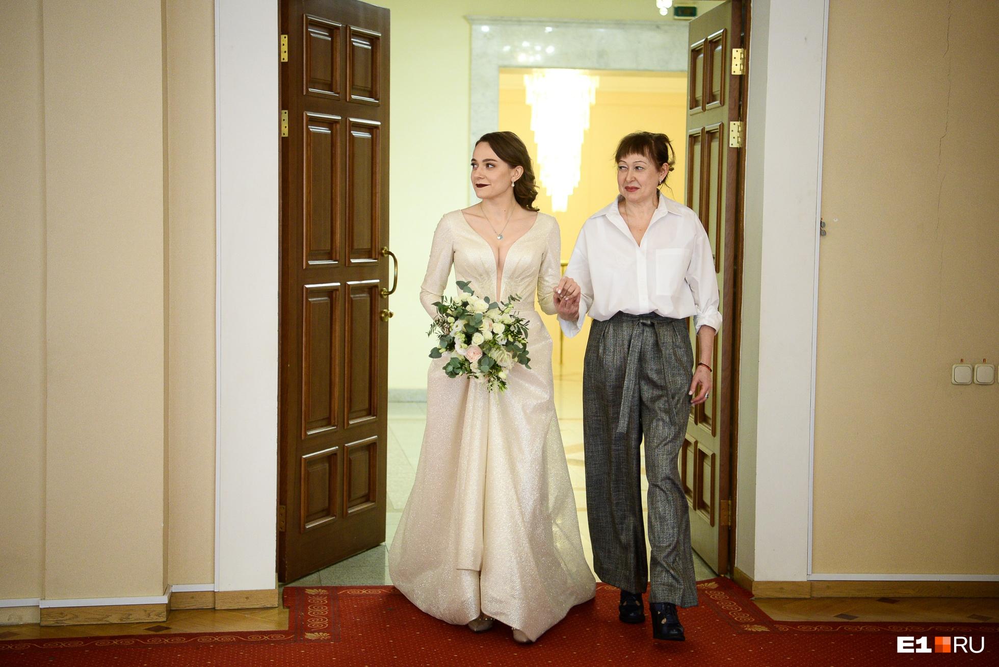 Это Александра входит в зал бракосочетания со своей мамой. Только сейчас Иван увидит свою невесту в свадебном платье