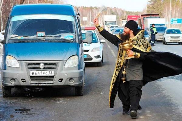Священник окропил трассу и дорожные знаки святой водой