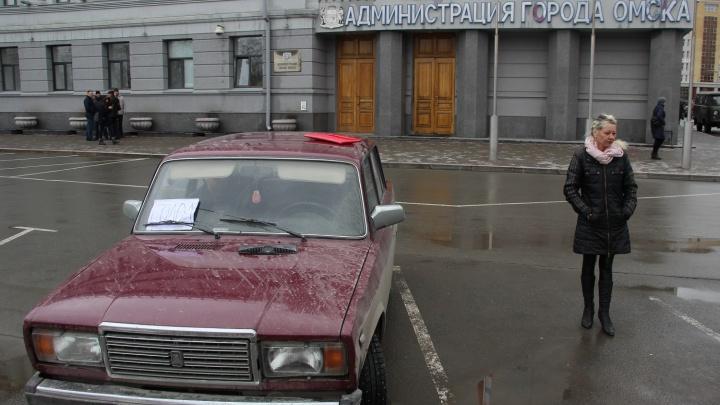 Возле мэрии припарковался автомобиль с надписью «Голод». В нём живут омские погорельцы