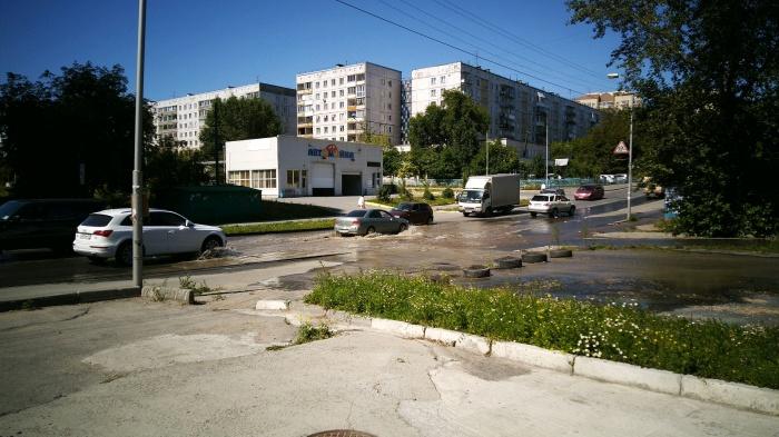 Разлившаяся по улице вода мешает проехать машинам