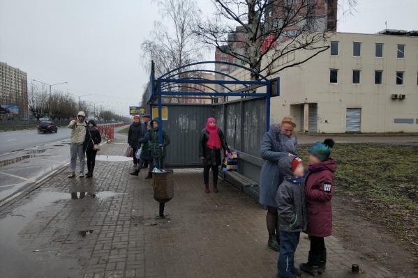 Люди мокнут под дождем и снегом, несмотря на то, что есть остановка