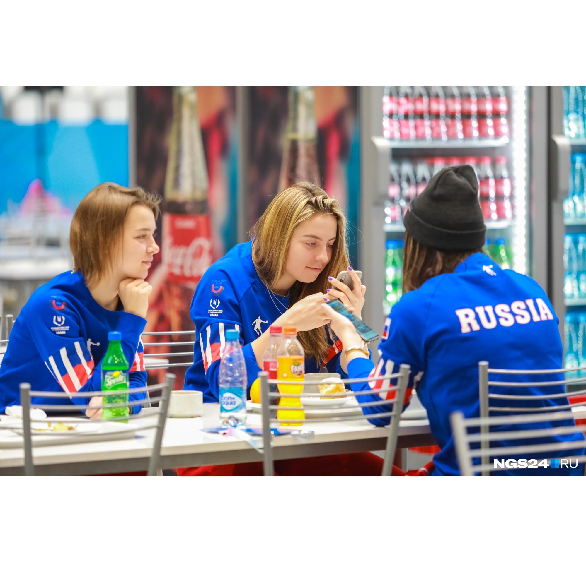 Рядом за столами сидят и спортсменки сборной России