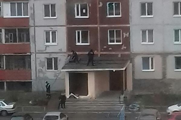 Тело мужчины лежало на козырьке подъезда жилого дома